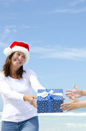 Beautiful looking and happy smiling mature woman wearing Santa Claus christmas hat is giving present to receiving hands, isolated with blue sky as background and copy space. photo