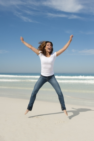 Happy cheerful young sexy woman jumping full of joy at beach with arms up Stock Photo - 16574264