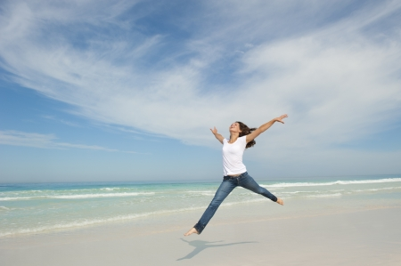 Happy cheerful young sexy woman jumping full of joy at beach with arms up