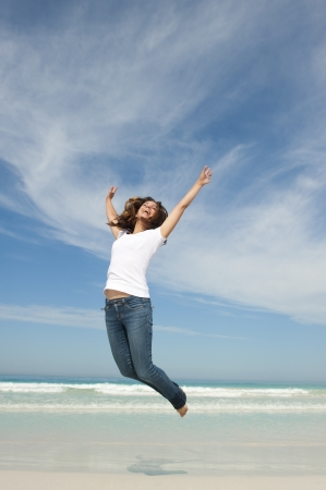 Happy cheerful young attractive woman jumping full of joy at beach with arms up Standard-Bild