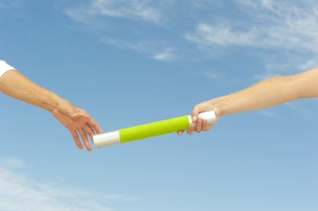 Hands of track and field athletes with relay baton, symbol for teamwork, partnership, cooperation, isolated with blue sky as background and copy space. Stock Photo - 16576537