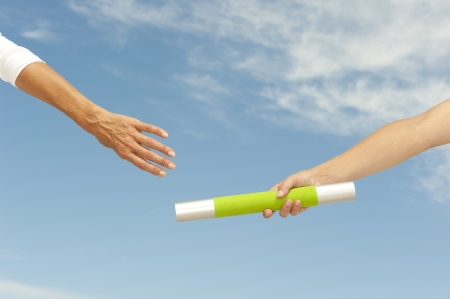 Hands of track and field athletes with relay baton, symbol for teamwork, partnership, cooperation, isolated with blue sky as background and copy space.