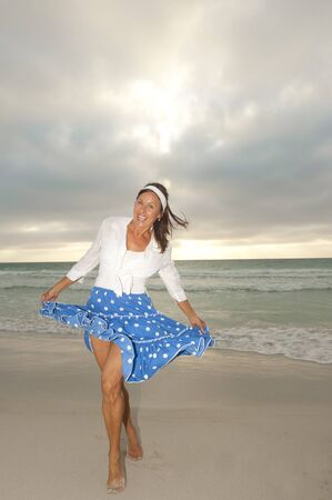 Portrait Sexy mature woman with white blouse and blue skirt at sunset beach photo