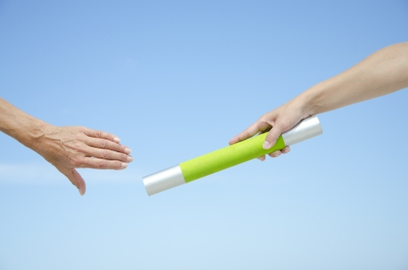 Hands of track and field athletes with relay baton, symbol for teamwork, partnership, cooperation, isolated with blue sky as background and copy space. photo