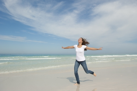 Beautiful looking young woman running cheerful with arms up at beach, isolated with ocean and sky as background and copy space.