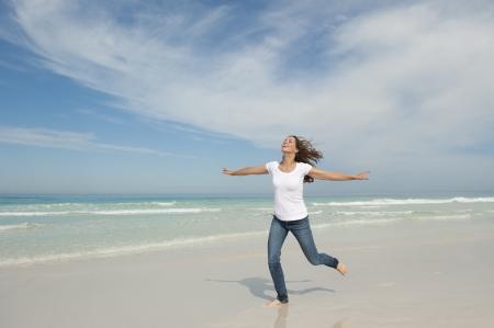 Bella donna cerca giovane in esecuzione allegro con le braccia aperte in spiaggia, isolato con mare e cielo come sfondo e copia spazio.