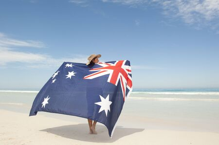 Attractive mature woman wearing akubra hat and with Australian flag around shoulder standing at tropical Australian beach, isolated with ocean and blue sky as background and copy space. Standard-Bild