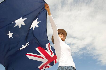 Upward view of Attractive mature woman wearing akubra hat and with Australian flag around shoulder, isolated with blue sky  and clouds as background and copy space.