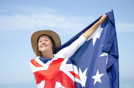 Ritratto di donna matura attraente che porta il cappello Akubra e con la bandiera australiana attorno alle spalle di posa isolato con cielo blu come sfondo e copia spazio. Archivio Fotografico