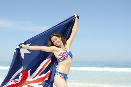Sexy happy young woman at beach, wearing Australian bikini and Australian flag, isolated with ocean and blue sky as background and copy space. Stock Photo