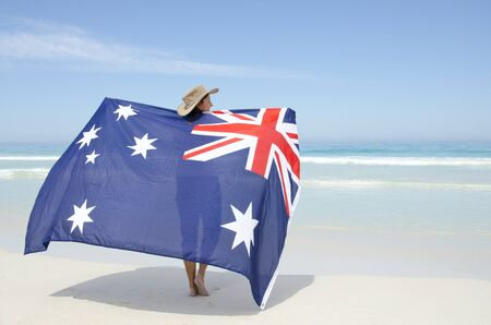 Attraente donna matura che indossa cappello Akubra e con la bandiera australiana in giro in piedi spalla a spiaggia tropicale australiana, isolato con mare e cielo azzurro come sfondo e copia spazio