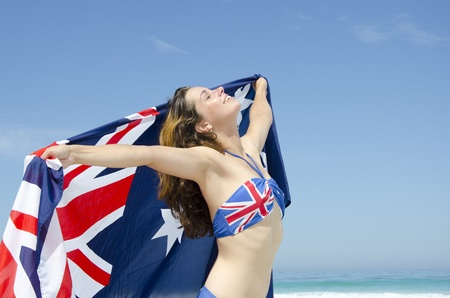 union beach: Sexy happy young woman at beach, wearing Australian bikini and Australian flag, isolated with ocean and blue sky as background and copy space. Stock Photo