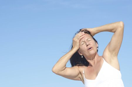 Portrait attractive Middle aged woman in menopause with headache, posing outdoor isolated with  blue sky as background and copy space. photo