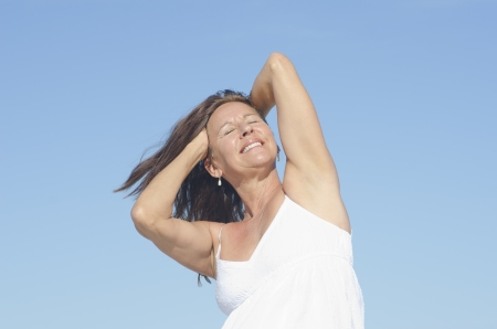Portrait happy attractive mature woman in white summer dress, relaxed with closed eyes and happy smile, isolated with blue sky as background. photo