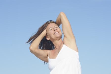 closed eyes: Portret gelukkige aantrekkelijke rijpe vrouw in witte zomerjurk, ontspannen met gesloten ogen en gelukkige glimlach, geïsoleerd met blauwe hemel als achtergrond. Stockfoto
