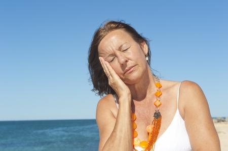 Ritratto sola donna matura con i sintomi dell'emicrania o la menopausa, isolati con mare e cielo azzurro come sfondo e copia spazio.