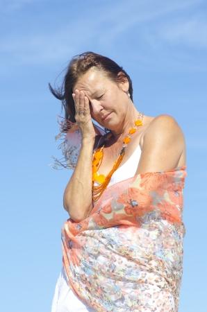 Ritratto Bella donna matura con i sintomi dell'emicrania o la menopausa, isolato all'aperto con cielo blu come sfondo.