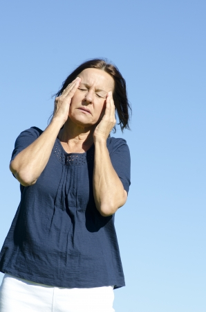 Portrait sad and stressed mature woman suffering migraine headache, isolated with blue sky as background. photo