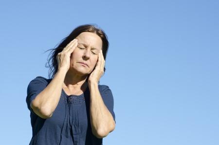 hormonas: Retrato maduro dolor de cabeza migraña triste y estresada mujer sufrimiento, aislada con el cielo azul como fondo.