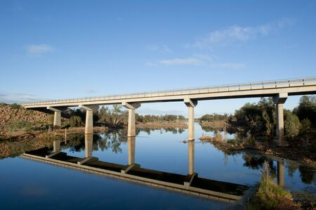 bank western: Highway bridge over Murchison River in Western Australia, with lush outback vegetation along the river bank and blue sky as background. Stock Photo