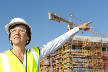 Mature female architect or construction engineer on building site supervising, wearing hardhat, with blurred background of construction site with crane. photo