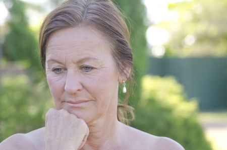 Outdoor portrait of sad and worried looking mature woman, isolated with blurred background photo