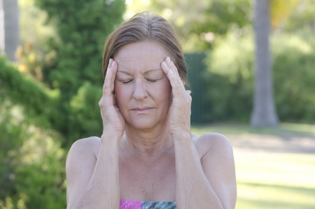 beautiful middle aged woman: Outdoor portrait of concerned mature woman with headache and hands at forehead, isolated with blurred background. Stock Photo