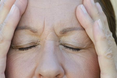 ojos tristes: Close up retrato de mujer preocupada con los ojos cerrados y las manos en la frente. Foto de archivo
