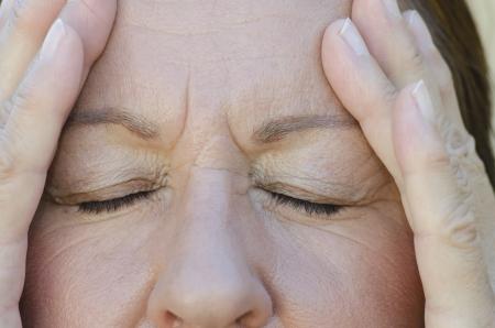 Close Up Ritratto di donna preoccupata con gli occhi chiusi e le mani sulla fronte.