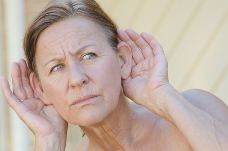 Portrait beautiful looking mature woman looking worried while listening with hands close to ears, isolated outdoor with blurred background. photo