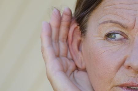 Ritratto bella donna in cerca maturo cercando curioso durante l'ascolto con le mani vicino alle orecchie, isolato all'aperto con sfondo sfocato.