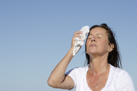 Portrait of stressed and exhausted looking middle aged woman trying to cool down face, isolated outdoor with blue sky as background and copy space.