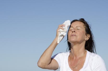 sudoracion: Retrato de estresado y agotado buscando mujer de mediana edad tratando de enfriar la cara, aislado al aire libre con el cielo azul como fondo y espacio de la copia.