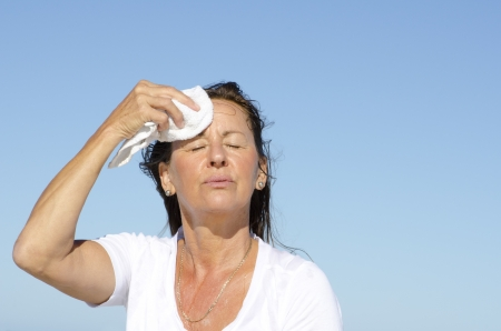 Portrait of stressed and exhausted looking middle aged woman trying to cool down face, isolated outdoor with blue sky as background and copy space. Stock Photo - 16766152