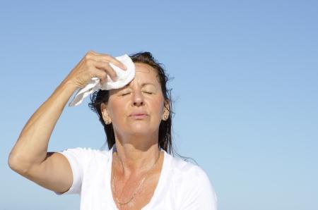 sudando: Retrato de estresado y agotado buscando mujer de mediana edad tratando de enfriar la cara, aislado al aire libre con el cielo azul como fondo y espacio de la copia.