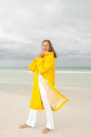 Portrait attractive mature woman with yellow  protective raincoat, isolated with ocean and cloudy autumn sky as blurred background and copy space. photo