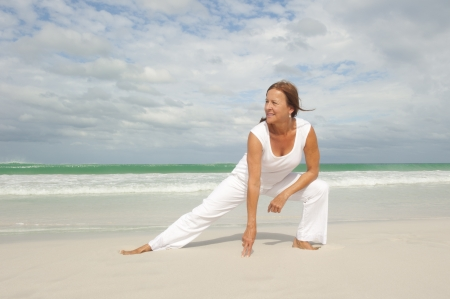Attractive fit and healthy middle aged woman doing stretch exercising confident and happy at beach, isolated with ocean and cloudy sky as background and copy space.