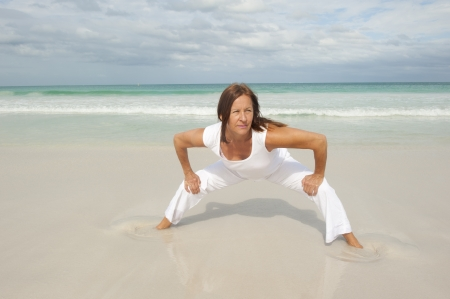 determined: Attractive fit and healthy middle aged woman doing stretch exercising confident at beach, isolated with ocean and cloudy sky as background and copy space.