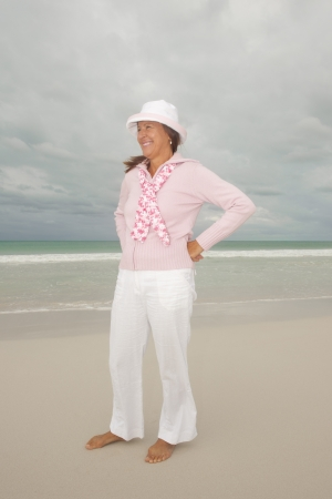 Attractive, joyful and confident looking middle aged woman at beach enjoying active retirement holiday, isolated with storm clouds in the sky and ocean as background and copy space. photo