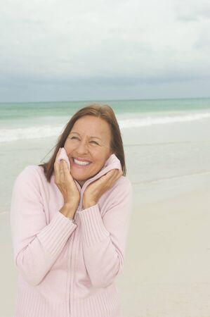middle aged woman smiling: Portrait Happy beautiful middle aged woman smiling joyful at beach holiday and active retirement, isolated with ocean and overcast sky as blurred background and copy space.