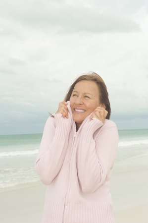 mature brunette: Portrait Happy beautiful middle aged woman smiling joyful at beach holiday and active retirement, isolated with ocean and overcast sky as blurred background and copy space.