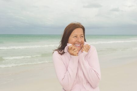 Portrait Happy beautiful middle aged woman smiling joyful at beach holiday and active retirement, isolated with ocean and overcast sky as blurred background and copy space. Stock Photo - 16848656