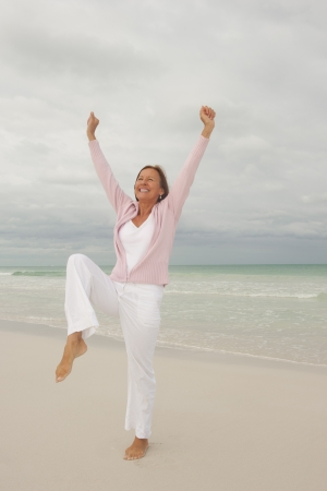 middle aged woman smiling: Portrait Happy beautiful middle aged woman smiling joyful and cheerful arms up at beach holiday and active retirement, isolated with ocean and overcast sky as blurred background and copy space.