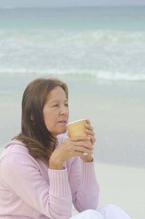 Portrait Attractive and relaxed middle aged woman enjoying leisure lifestyle with a hot drink (coffee or tea) at beach, with ocean as blurred background and copy space. photo