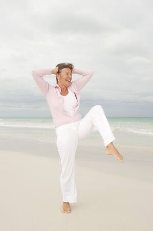 Portrait Happy beautiful middle aged woman smiling joyful and cheerful arms up at beach holiday and active retirement, isolated with ocean and overcast sky as blurred background and copy space. Stock Photo - 16880806