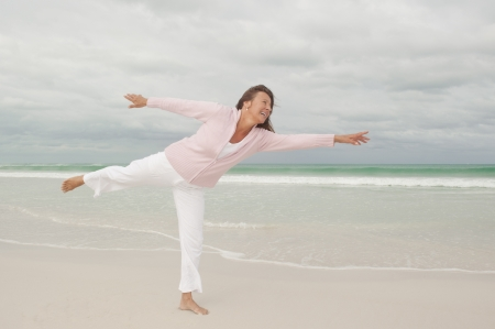Portrait attractive and happy Active retired senior woman stretching exercise at beach, isolated with ocean and storm clouds as background and copy space. photo