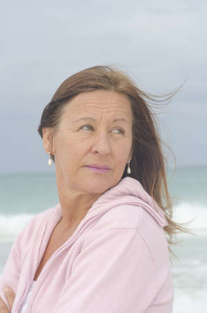 Portrait attractive middle aged woman enjoying active retirement, confident looking, isolated with ocean as blurred background. Stock Photo - 16880811