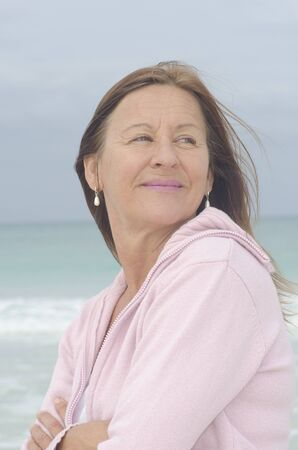 Portrait attractive middle aged woman enjoying active retirement, happy smiling, isolated with ocean as blurred background. Stock Photo - 16873634