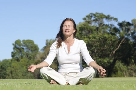Attractive middle aged woman sitting relaxed with closed eyes in park meditating, isolated with trees and sky as blurred background and copy space.