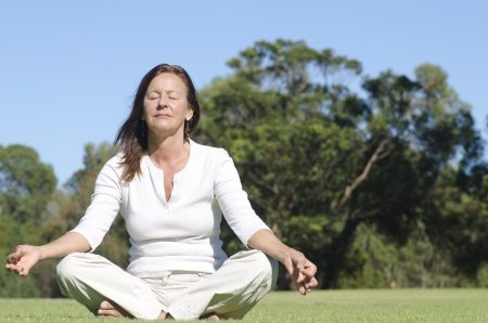 serenety: Attractive middle aged woman sitting relaxed with closed eyes in park meditating, isolated with trees and sky as blurred background and copy space.
